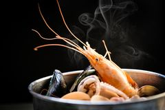 Shellfish seafood plate with shrimps prawns mussel squid ocean gourmet dinner seafood cooked boiled in hot pot. With herbs and spices on dark background stock images