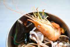 Shellfish seafood plate with shrimps prawns mussel squid ocean gourmet dinner seafood cooked boiled in hot pot. With herbs and spices on table background stock image