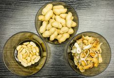 Peeling peanuts. A bowl of peels and clean peanuts on the plate. View from above. Shelling peanuts, nutshell in a bowl and clean peanuts on the plate. View from Stock Photo