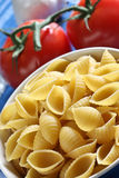 Shells. Pasta inside  bowl with red tomato behind Royalty Free Stock Photo