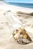 Shells in the bottle on the beach Stock Photography