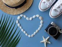 Shells, een overzees ster, tennisschoenen, een tropisch blad, een de zomerhoed en een camera stock foto's