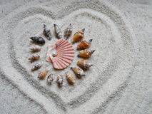 Shells in the heart on gray sand - selective focus Stock Photography