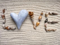 Shells in the heart on gray sand - selective focus Royalty Free Stock Image