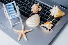 Shells and holiday mood Online booking on a notebook royalty free stock image