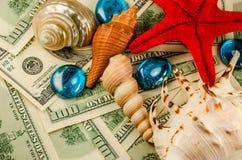 Shells on money. Shells starfish and water drops on dollars Stock Photo