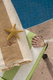 Shells near the pool. Chaise lounge with towel, starfish and shell in the edge of a swimming pool royalty free stock photos