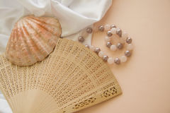 Shells and pearls on pink background. Spa concept background in pink and beige colors Royalty Free Stock Photo