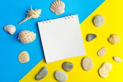 Shells and pebbles with laptop On blue and yellow geometric paper background . The concept of planning a summer vacation. Create royalty free stock photography