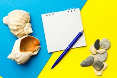 Shells and pebbles with laptop On blue and yellow geometric paper background . The concept of planning a summer vacation. Create stock images