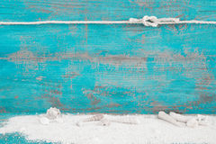 Shells and sand in front of turquoise vintage wood for a wooden Royalty Free Stock Photography