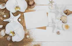 Shells, seastars and a blank postcard. Holiday beach concept with shells, seastars, orchids  and a blank postcard Stock Photo