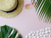 Shells, tropical leaves, summer hat and heart-shape sunglasses on the pink background royalty free stock photos