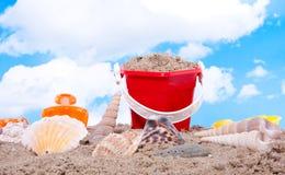 Shells und Plastikstrandspielwaren Lizenzfreies Stockbild