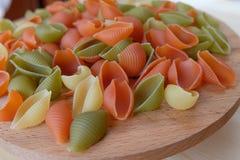 Shells van tri-kleurendeegwaren op het hout Stock Fotografie