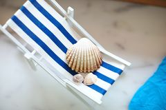 Shells of various sizes lie on a little vintage decoration striped beach chair with a blue sea, top view. Shells of various sizes lie on a little vintage stock photos