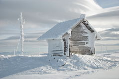 Shelter and antenna. Small mountain shelter house and big antenna covered with lots of snow and icicles Stock Photography