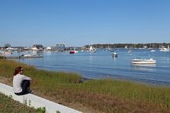 Shelter Island Travel. A visitor looks at boats on the water in Shelter Island, NY Stock Photos