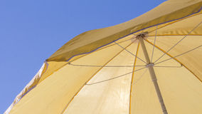 Shelter from the sun. Beach yellow umbrella under the sunny blue sky royalty free stock images