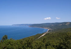 Sheltered bay and beach, with wandering road. View of a sheltered ocean bay and beach/coastline with road wandering through foreground and forest; Cape Breton royalty free stock images