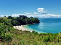 Sheltered beach surrounded by hills and trees. Sheltered sandy beach on Motuihe Island near Auckland surrounded by hills with trees and bushes Royalty Free Stock Photo
