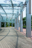 Sheltered Walkway. Glass sheltered walkway with wooden flooring and perforated pillar Royalty Free Stock Image