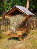 Sheltered wooden feeder fully filled with hay. And prepared for feeding wild animals throughout a winter. A small wooden fence can be seen in the background royalty free stock photography