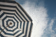 Sheltering From Sun Under Beach Umbrella. 