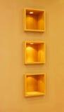 Shelves. Three wooden rectangular shelves in brown wall Stock Image