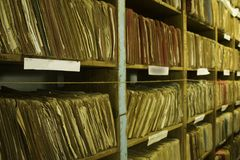 Shelves of ageing paper file records. Wooden shelves packed full of ageing paper files in cardboard folders royalty free stock images
