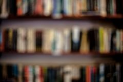 Shelves with books in a blurred background. Abstract colorful blurred background with books. Learning concept with blurred library royalty free stock photos