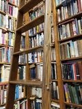 Shelves of Books in a Library. A rolling ladder waits to be used to get the out of reach book for the reader as the books wait on the floor to ceiling shelves Stock Images