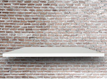Shelves and brick wall. Empty top white shelves and brick wall vintage background. For product display and advertising and promotional purposes Royalty Free Stock Photo