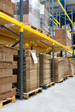 Shelves with cartons in warehouse. Shelves with carboard heaps and cartons in warehouse Royalty Free Stock Image