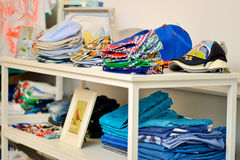 Shelves with clothes for baby. In natural light Stock Photos