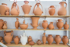 Shelves with different brown clay  jars and pots. Made by greek artists Royalty Free Stock Photography