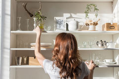 Shelves with different crockery. Female taking the candlestick from the white shelves with various crockery. Back view Stock Image