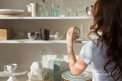 Shelves with different crockery. Female taking the candlestick from the white shelves with various crockery. Back view Stock Photography