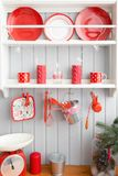 Shelves with dishes. Interior light grey kitchen and red christmas decor. Preparing lunch at home on the kitchen concept. Interior light grey kitchen and red Stock Photos