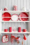 Shelves with dishes. Interior light grey kitchen and red christmas decor. Preparing lunch at home on the kitchen concept. Interior light grey kitchen and red Royalty Free Stock Photo