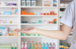 Shelves of drug in the pharmacy drugstore. Medical pharmacist woman presenting and showing copy space for product or text with blur shelves of drugs in the Stock Image