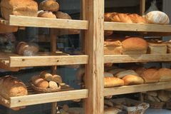 Shelves filled with freshly baked loaves of bread. Diplayed in shop window in town of Sidmouth, East Devon stock image