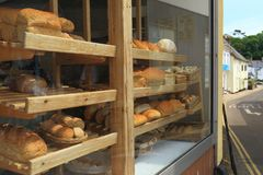 Shelves filled with freshly baked loaves of bread. Diplayed in shop window in town of Sidmouth, East Devon stock photography