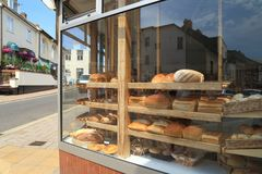 Shelves filled with freshly baked loaves of bread. Diplayed in shop window in town of Sidmouth, East Devon stock photo