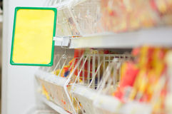 Shelves with food and info label in supermarket Royalty Free Stock Images