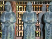 Shelves full of identical Japanese relgious staues. Hundreds of Japanese religious staues for sale to place at shrines. The staues are identical, and are Royalty Free Stock Photo