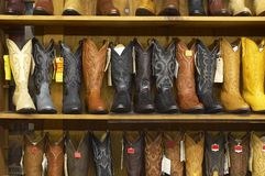 Shelves full of new cowboy boots. Shelves full of many new cowboy boots with price tags in store Royalty Free Stock Images
