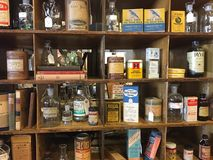 Shelves full of vintage boxes, bottles, can and books. Royalty Free Stock Photos