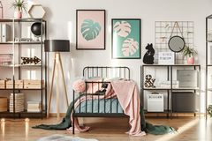 Shelves in girl bedroom. Metal shelves with decorations, botanical posters and comfy bed in a girl bedroom interior stock photo