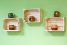 Shelves made of wooden boxes with clay bowls Stock Image